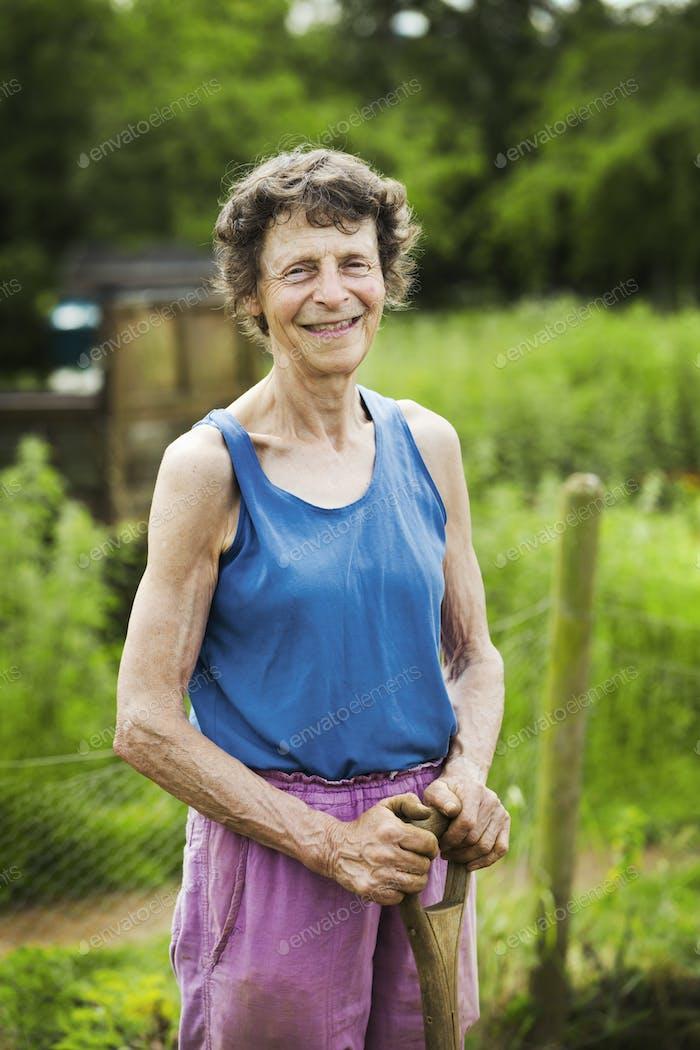 Eine Frau, die eine Schaufel auf einer Farm hält.