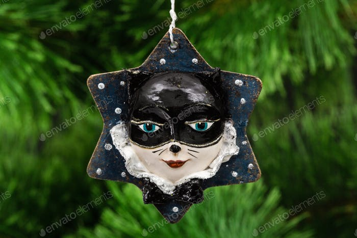 Festive decoration in the shape of a cat mask, on a Christmas tr