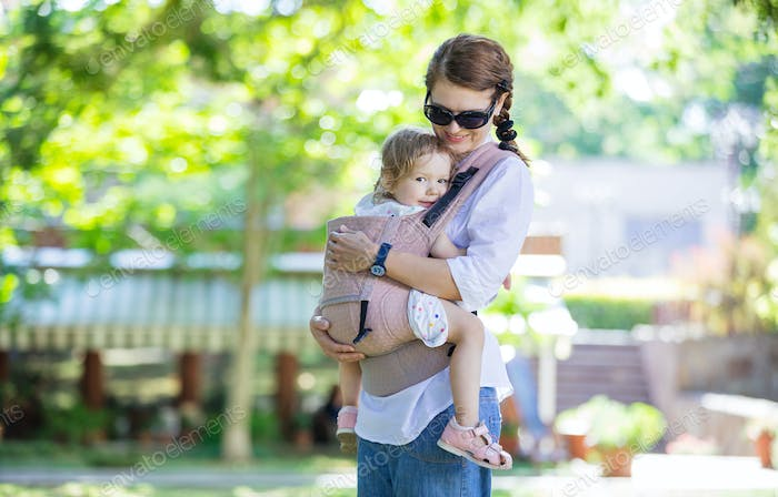 Caucasian woman and her daughter in baby carrier in park