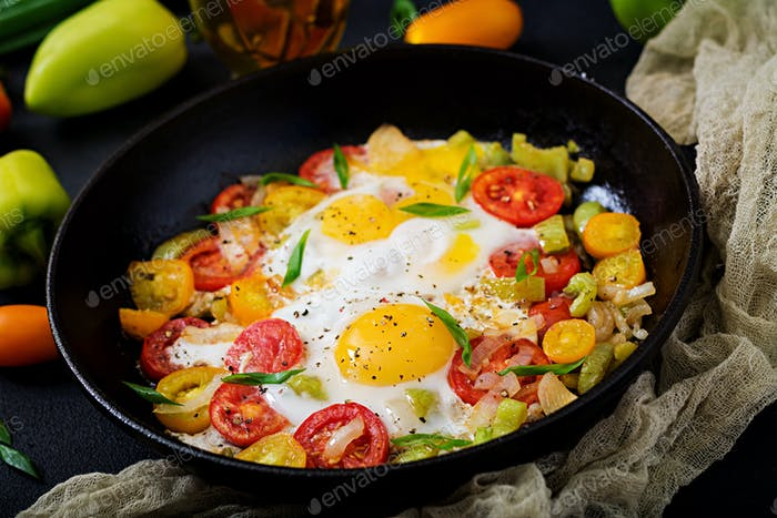 Fried eggs with vegetables - shakshuka in a frying pan on a black background
