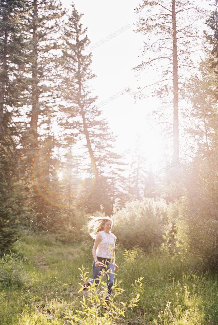 A woman running through a sunlit forest.