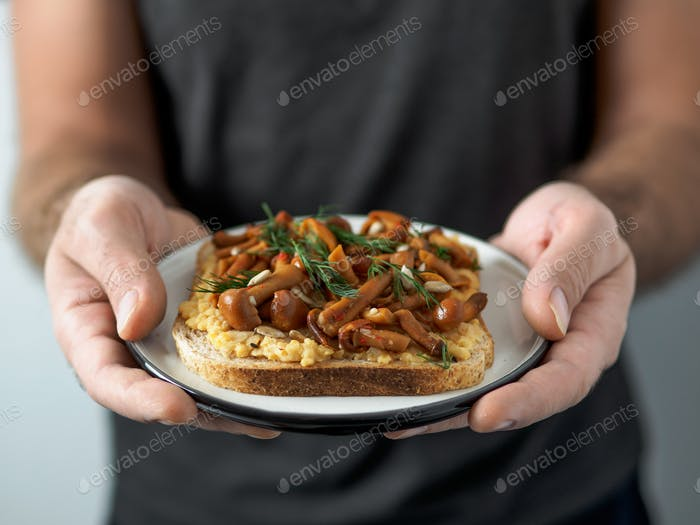 Vegan sandwich with mushrooms in male hands