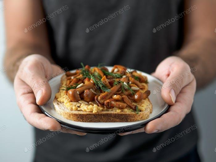 Vegan sandwich with mushrooms in male hands