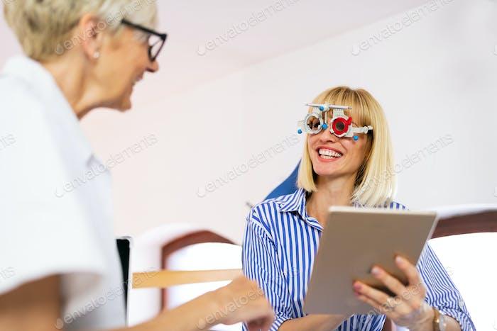 Senior Frau Optometrist untersucht Patienten in der modernen Augenklinik