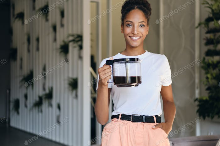 Young attractive smiling African American woman with coffee pot happily looking in camera in office