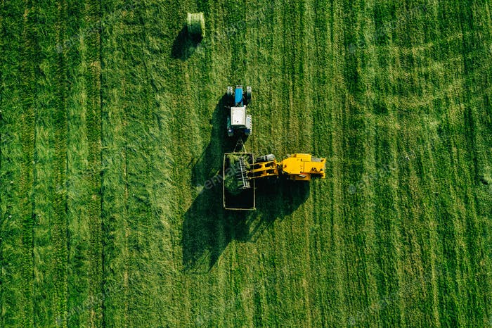Aerial view of harvest field with tractor moving hay bale