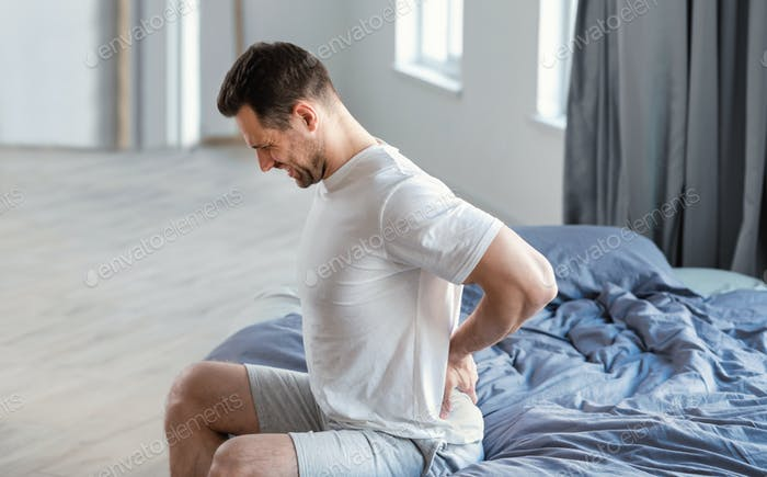 Man Massaging Aching Back Sitting In Bed At Home