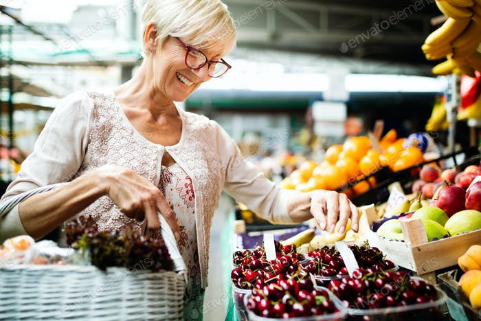 Picture of mature woman at marketplace buying vegetables