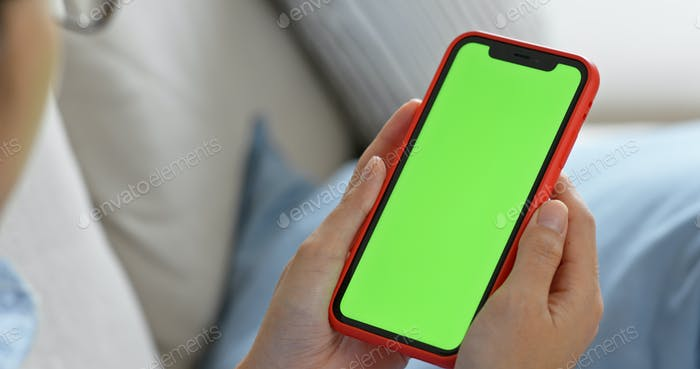 Woman hold with green screen of cellphone at home