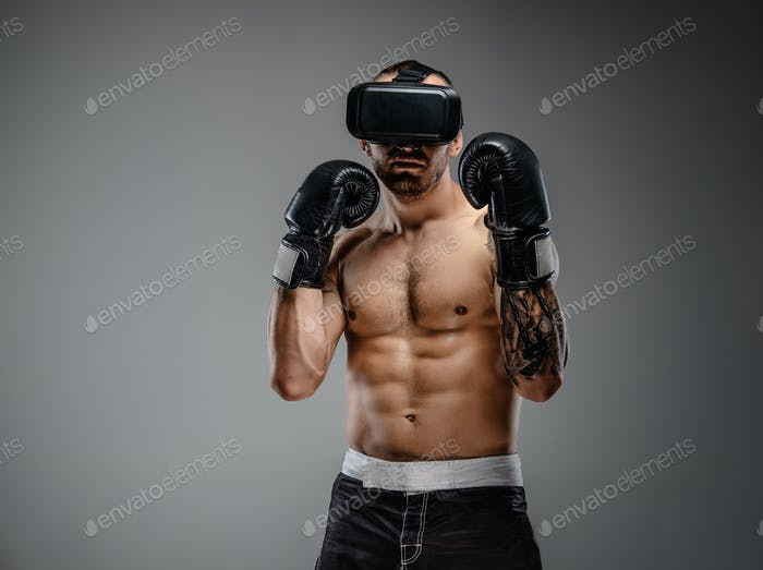 Shirtless brutal boxing fighter in virtual reality glasses.