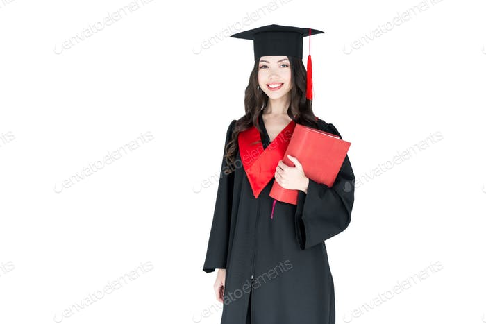 Beautiful young smiling brunette woman in mortarboard holding book  isolated on white