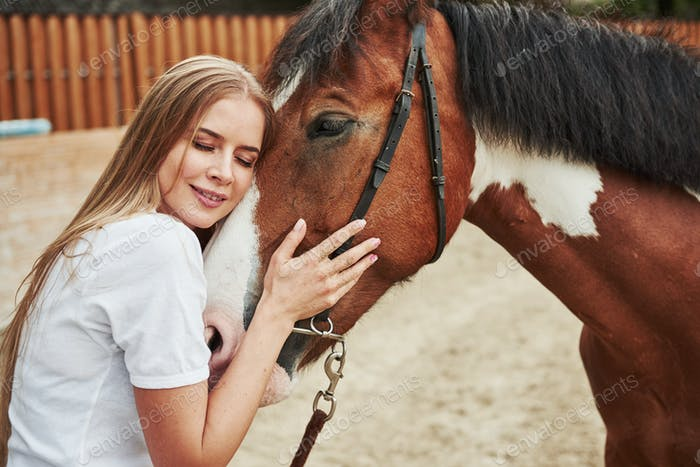 Girl is hugging a horse. Happy woman on the ranch at daytime