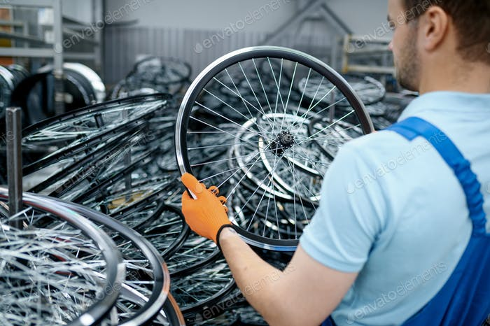 Mechanic in uniform holds bicycle wheel on factory