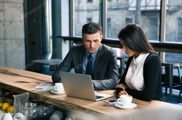 Thumbnail for Businessman and businesswoman using laptop in cafe