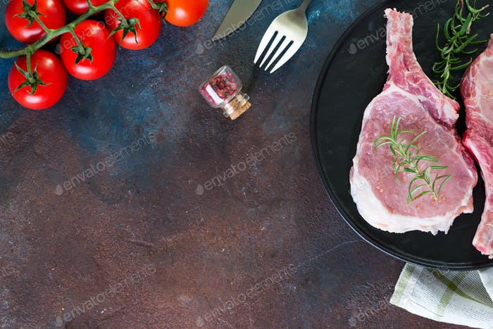Raw lamb ribs marinating with buna-shimeji and tomato in a grill pan on a dark stone background with