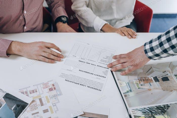 ImmobilienAgentur. Junges Paar Unterzeichnung Finanzierungsvertrag