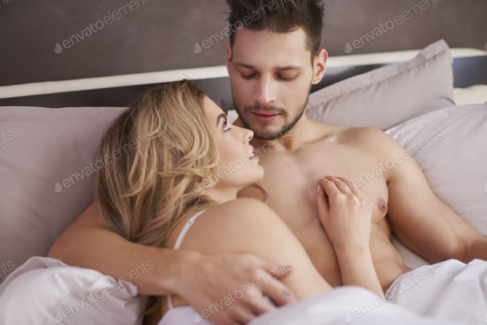 Beautiful couple lying down in the bed