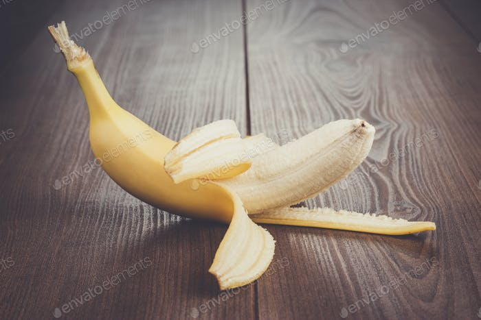 fresh peeled banana on the brown background