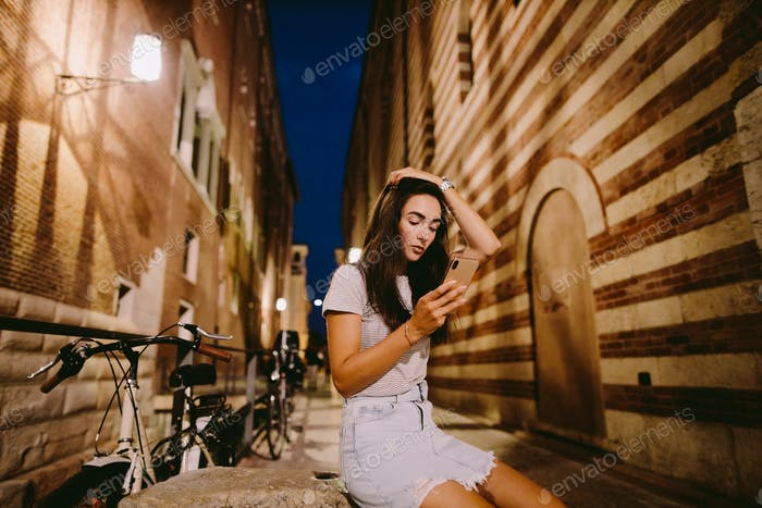 woman using smartphone in the evening outdoors