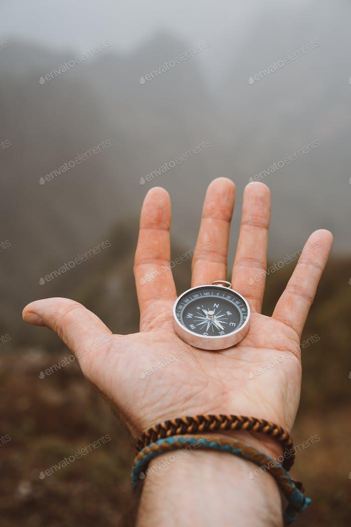 Hand hält einen Kompass. Silhouette der monumentalen Bergformation im Hintergrund
