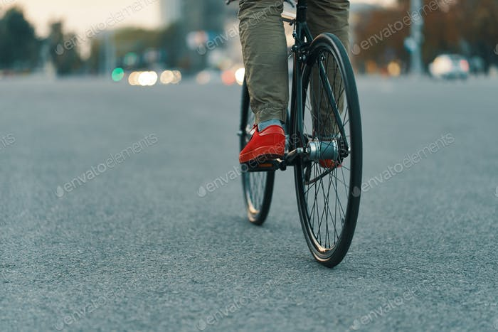 Closeup of casual man legs riding classic bike on city road