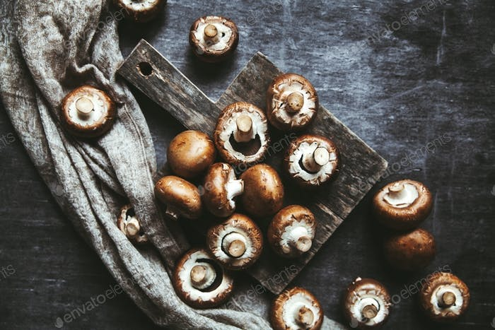 Royal mushrooms on a black background with a vintage board and a kitchen towel