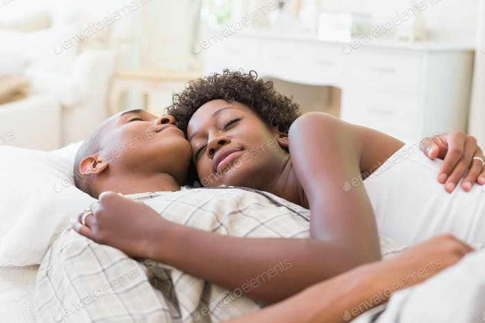 Happy couple lying in bed together at home in the bedroom