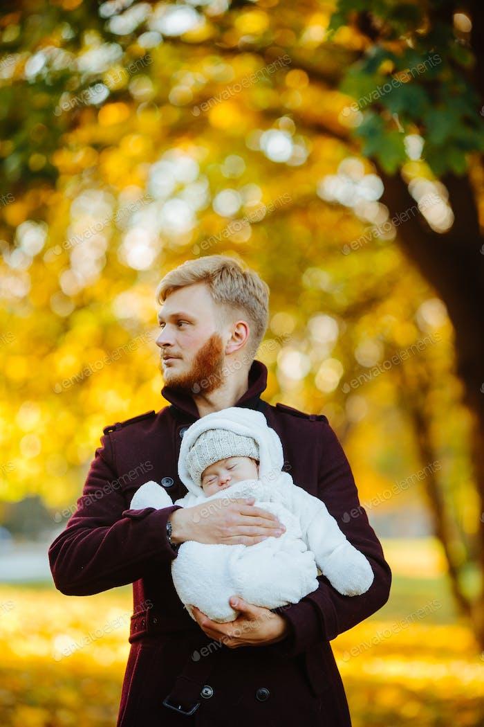 dad and newborn son in autumn park