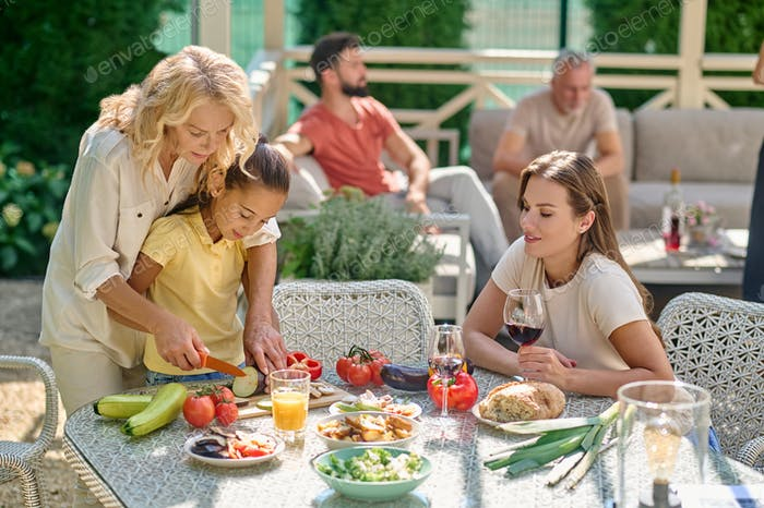 Women cutting veggetables for the dineer and looking involved