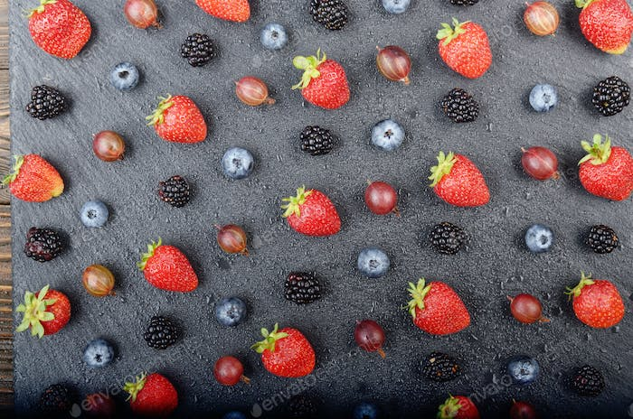 Flat lay view at ripe bilberry strawberry raspberry blackberry a