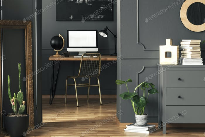 Real photo of dark living room interior with gold decor, fresh p