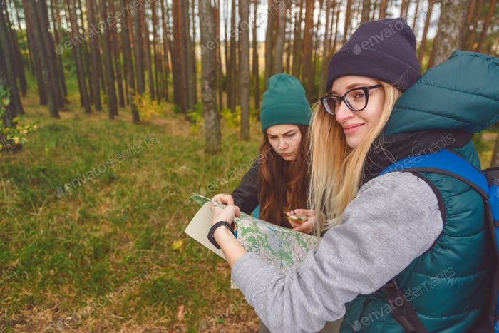 Two young tourist determine the route map and compass.