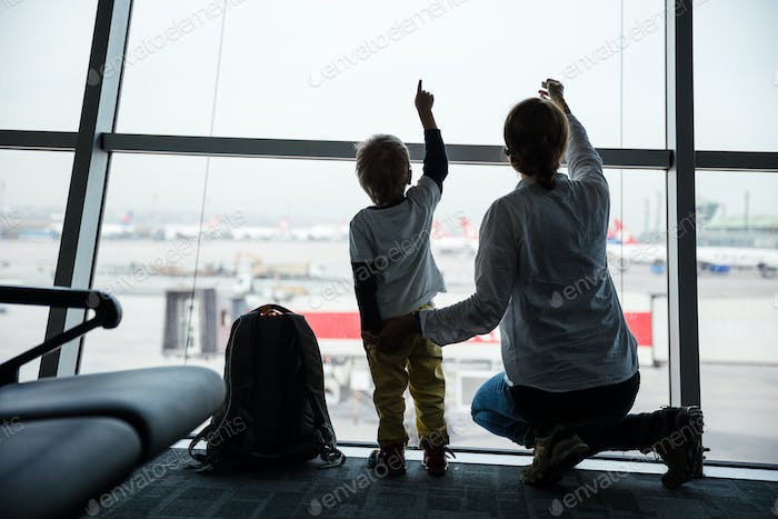Mother and son pointing to taking off airplanes while looking through window in airport