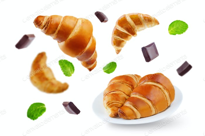 Flying croissants with chocolate and mint leaves isolated