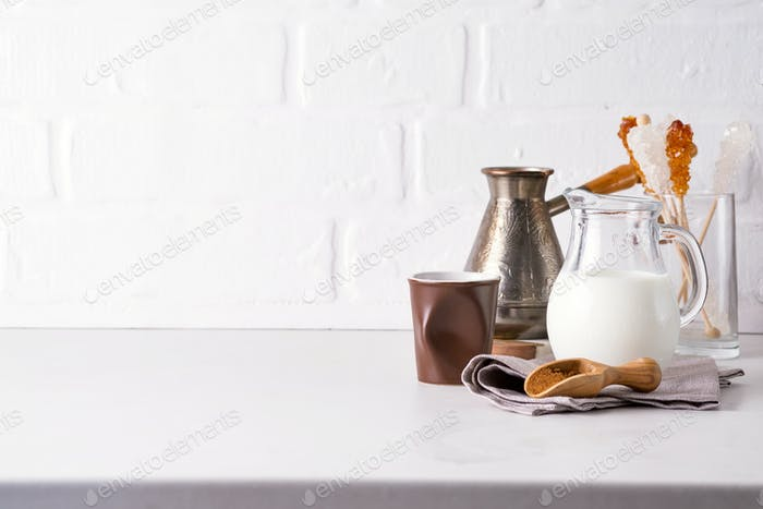 Jug of milk and ground coffee for making a drink at home on a stone countertop against a white