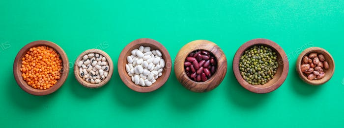 Assortment of legumes in wooden bowls on green background, isolated, top view, banner.