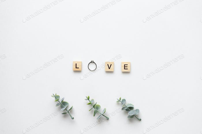Wooden letters with engagement ring spelling love, with oregano