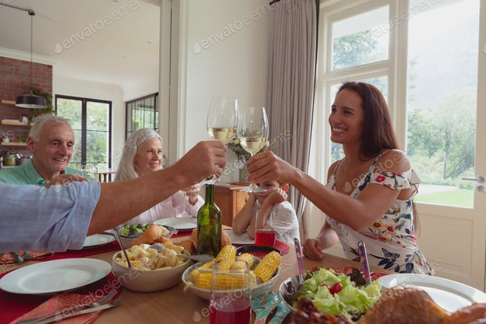 Happy Multi-generation Caucasian family toasting glasses of champagne on dining table at home