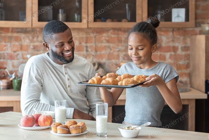 Cute girl holding tray with freshly baked croissants