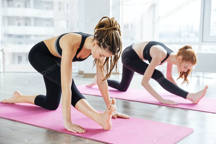 Two women stretching and practicing yoga in studio