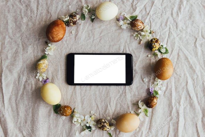 Telefon mit leerem Bildschirm im rustikalen Osterkranz mit Eiern und Blumen flach legen. Jahreszeiten-Grüße