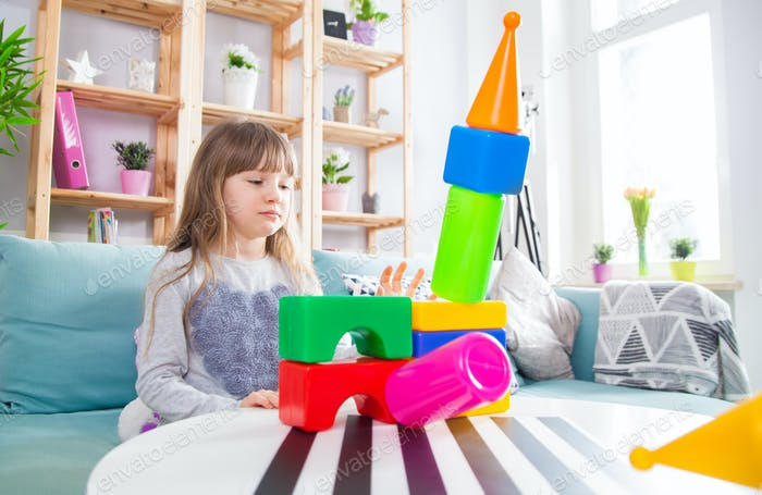 Cute little girl playing with blocks at home