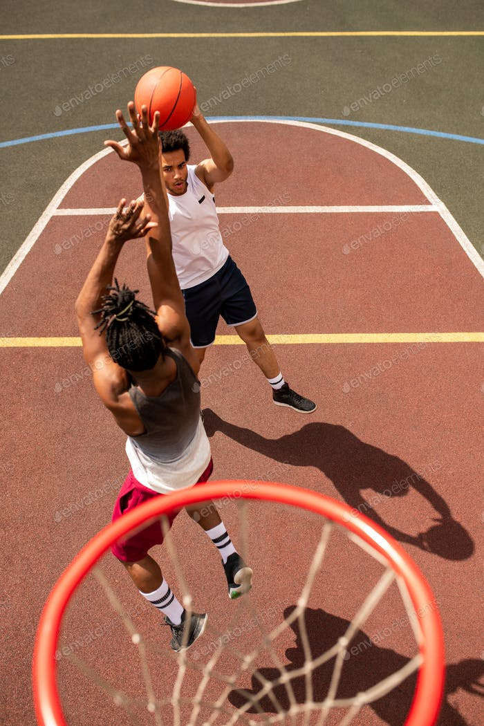 One of young intercultural basketball players attacking the ball of rival