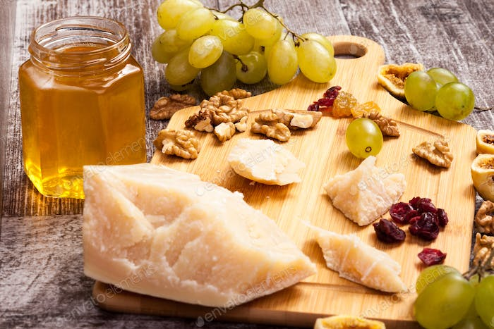 Honey, grape, different type of cheese and nuts on wooden backgr