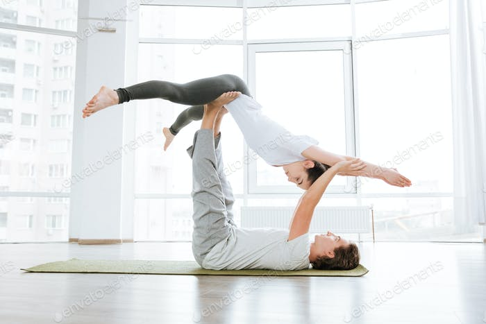 Man and woman doing acro yoga in pair in studio