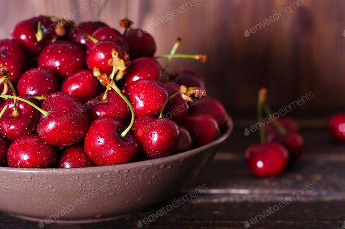 Fresh cherries in plate on dark wooden background with copy space. Summer and harvest concept