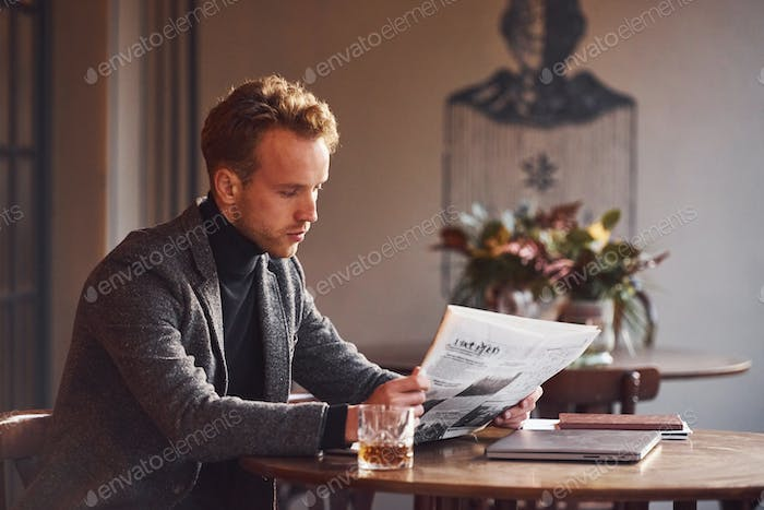 Portrait of modern young guy in formal clothes that sits in the cafe and reads newspaper