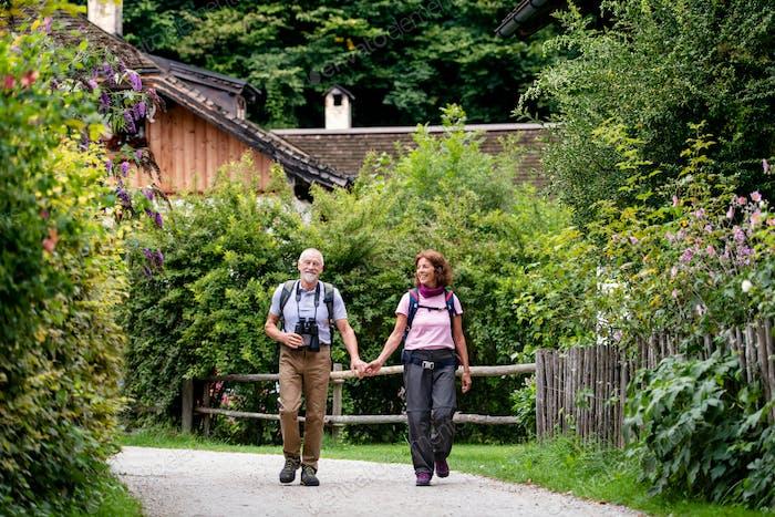A senior pensioner couple with binoculars hiking, walking.