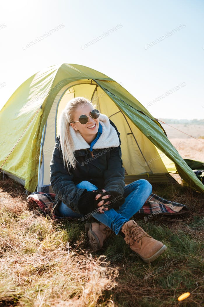 Woman in sunglasses and boots sitting near tent at campsite