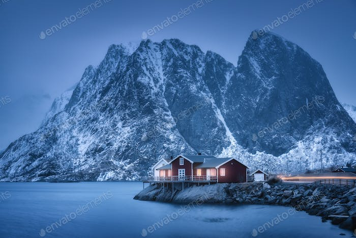 Red rorbu on sea coast and snow covered mountain at dusk